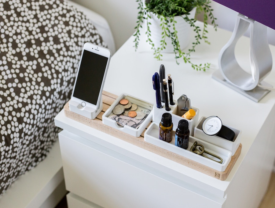 A bedside organiser containing a phone, change, pens and other assorted clutter