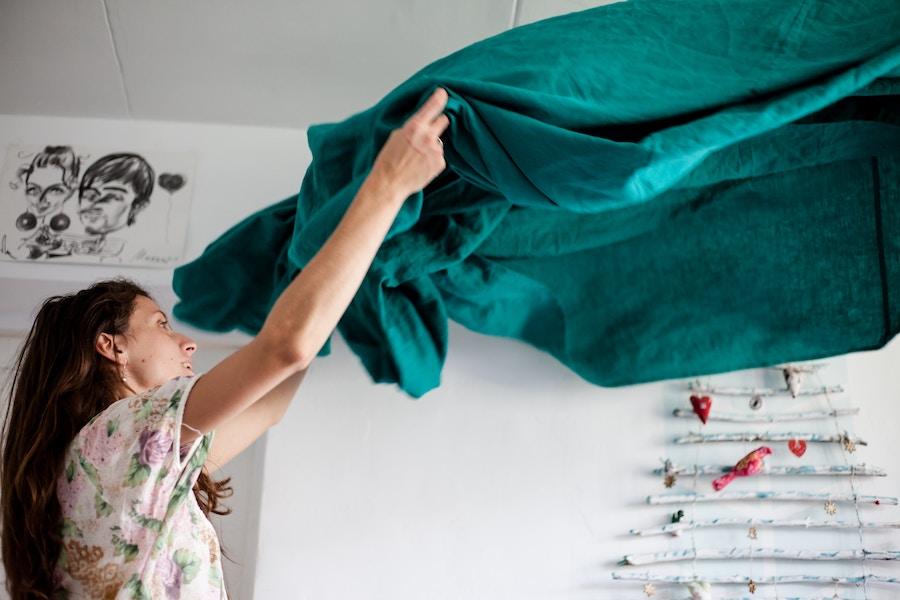 A woman changing dark green sheets