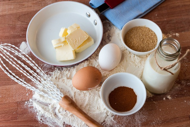 A kitchen counter with baking essentials including butter, eggs, flour and sugar