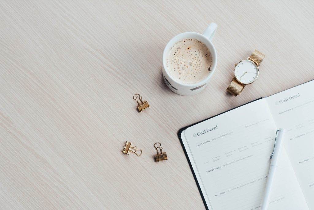 A diary lying open on a wooden table beside mug of coffee