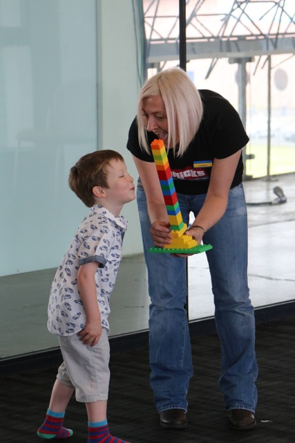 Carre from Bricks 4 Kidz Glasgow shows a young boy a tower of Lego
