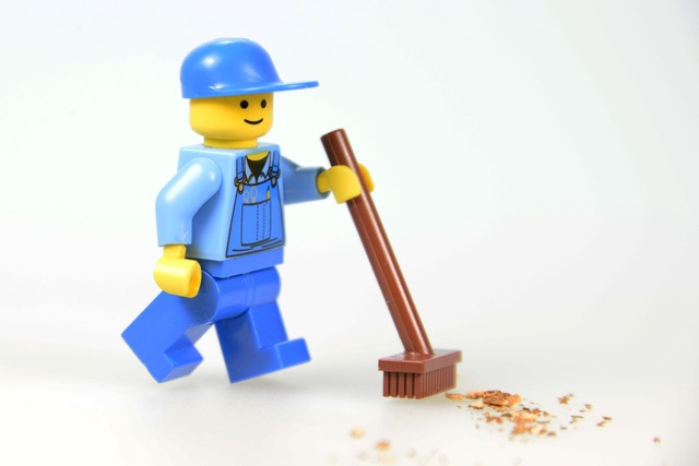 A Lego figure holding a broom and sweeping crumbs